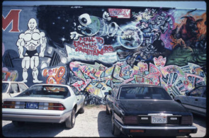 two cars in front of spray paint mural