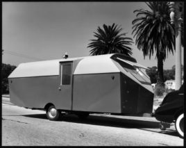 vintage, 1940s camper trailer attached to car; palm trees in background