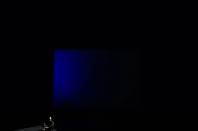 man alone on stage in front of blue projection screen