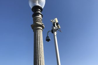 streetlight and security camera against a clear blue sky