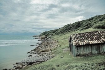 run down cottage on a green hill over looking a gloomy shoreline