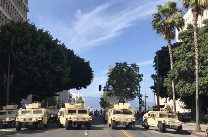 six tan military humvees blocking a los angeles intersection