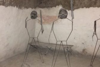 wire statues of people wearing gas masks and holding metal weapons in an empty cell