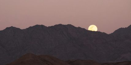 moon rising over mountain range at dusk